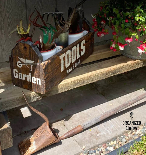 Photo of vintage garden tools in stenciled rustic toolbox