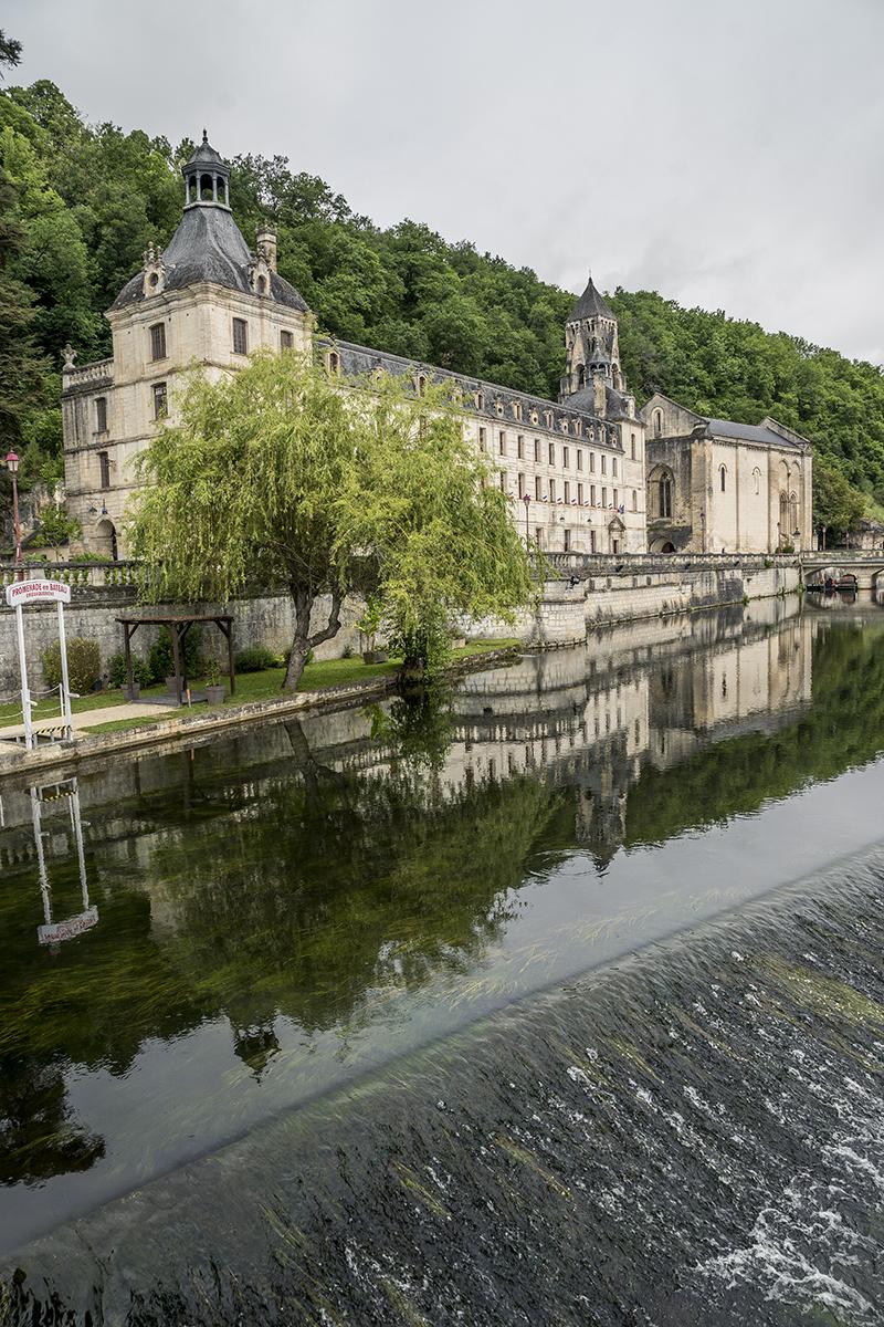 Vista de Brantome, en el Perigord, Francia, del puente de piedra y la abadía benedictina de Saint-Pierre