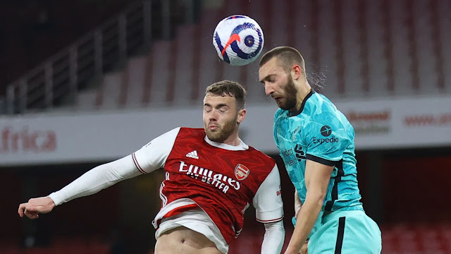 Arsenal defender Callum Chamber and Liverpool defender phillips challenging for the ball