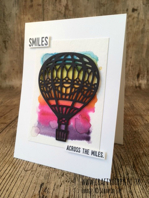A greetings card showing a die-cut black hot air balloon on a water-coloured rainbow background showing the sentiment 'smiles across the miles'