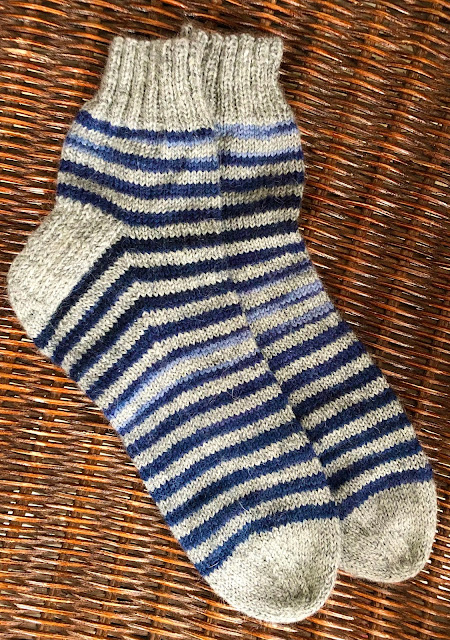 Socks knitted with DROPS Fabel light grey and deep ocean