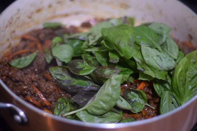 The basil being added to beef in the pan.
