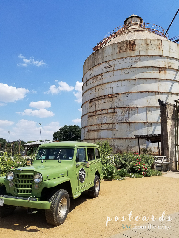 old green jeep and tall white metal silo