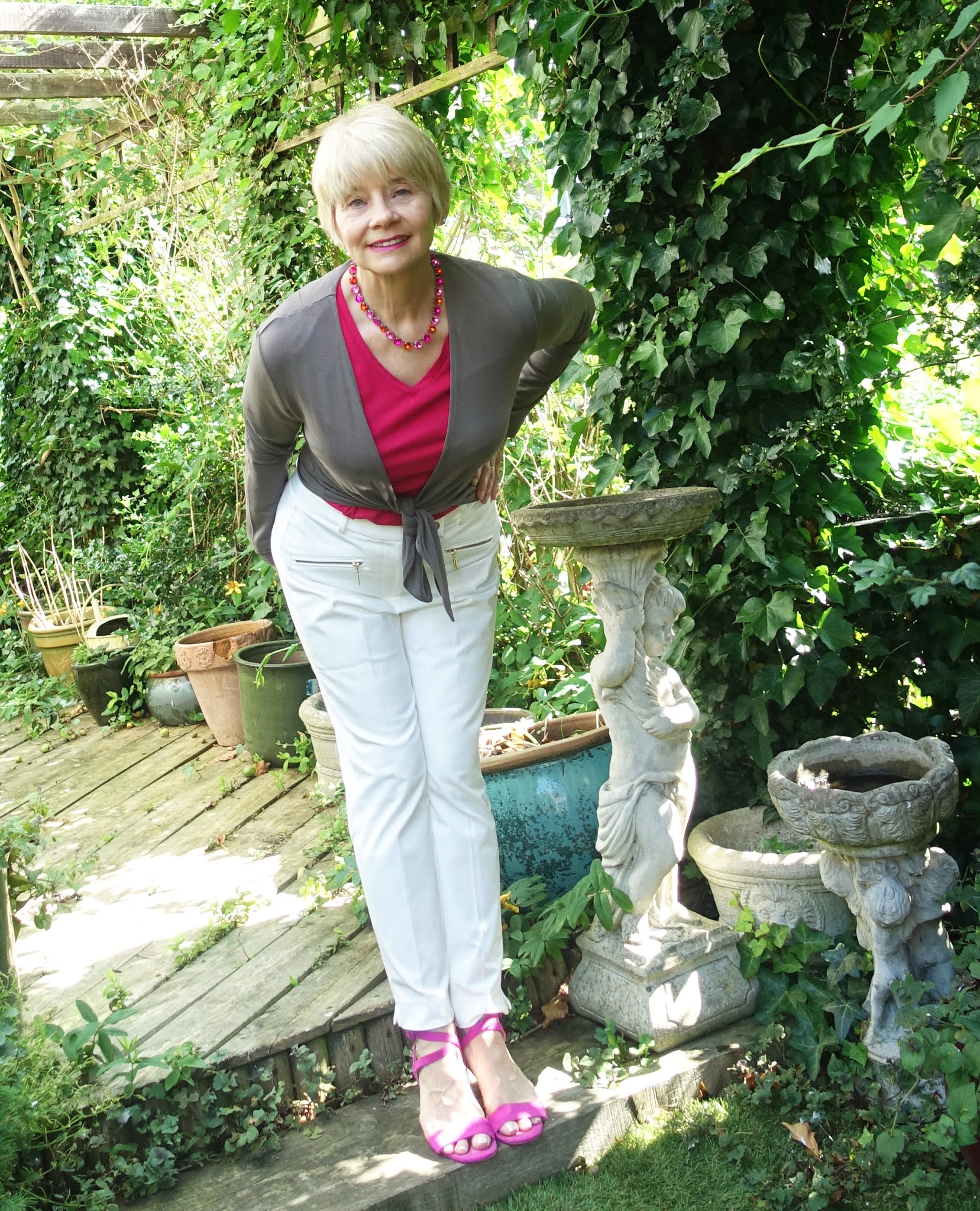 Over 50s blogger Gail Hanlon from Is This Mutton in the garden wearing white trousers, Kettlewell Mole short tie wrap and top in Sangria with fuchsia sandals