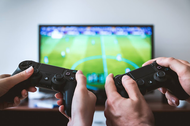 Two people playing a football video game on a PS4