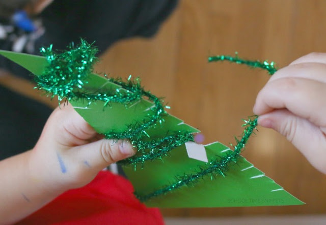 Adding garland to christmas tree craft for kids