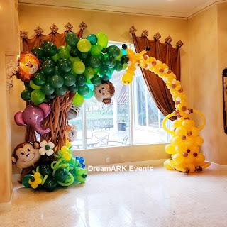 Safari theme balloon arch with balloon tree and giraffe balloon sculpture