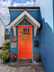 Bright orange door on a blue house in Carlingford Town