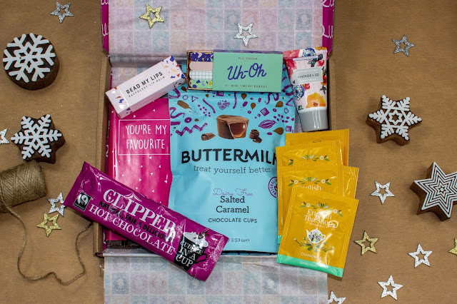 A thin cardbox with treats inside including: hot chocolate, chocolate bar, caramel cups, lip balm, nail files, tea bags and handcream.