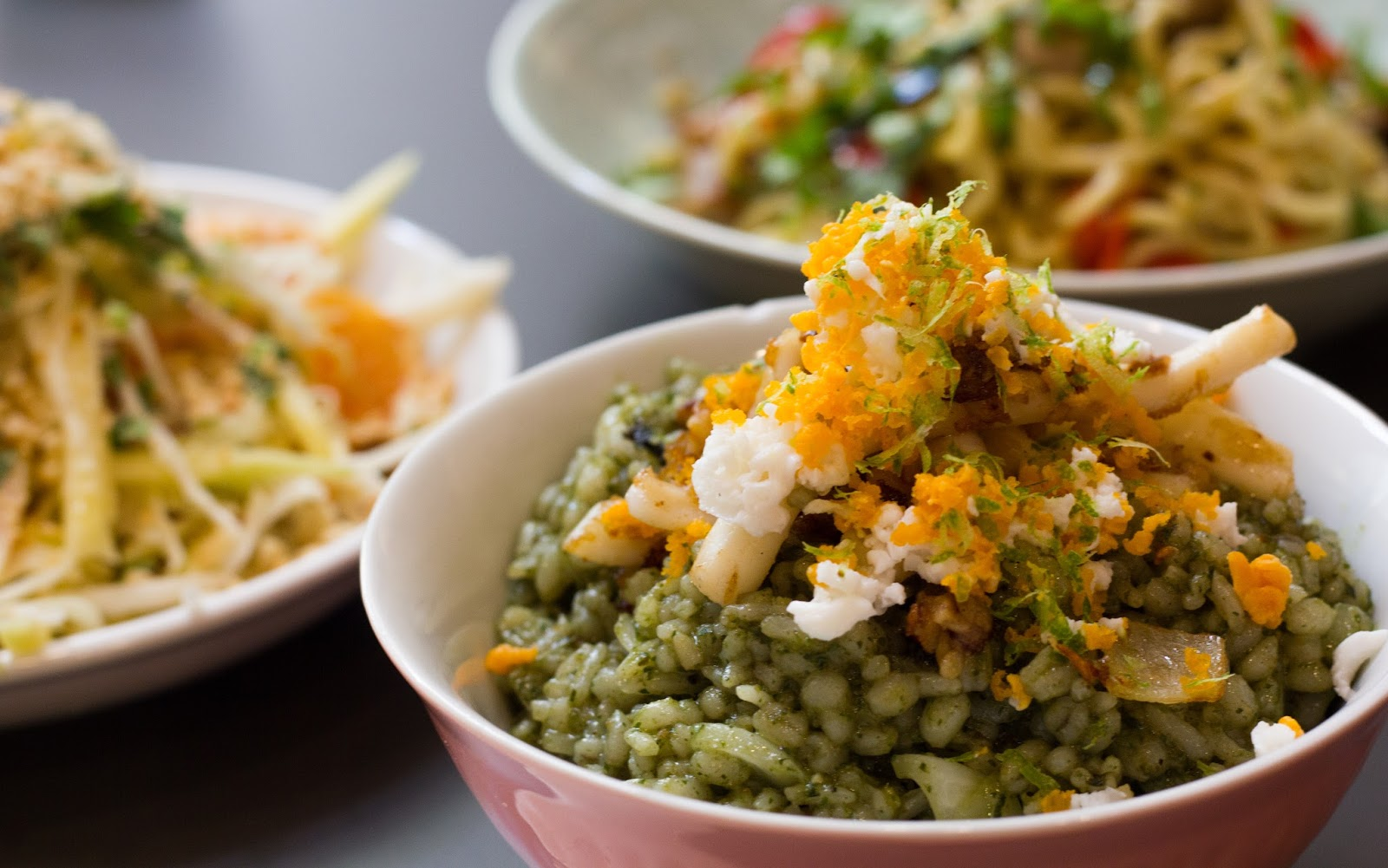 A bowl of ulam pesto, shaved salted egg, crispy dried shrimps, sauteed  fresh squids.