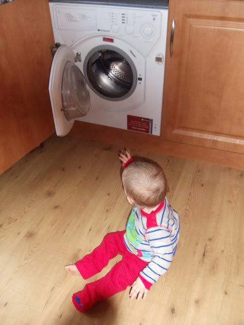 little boy sitting on the floor staring at an open washing machine