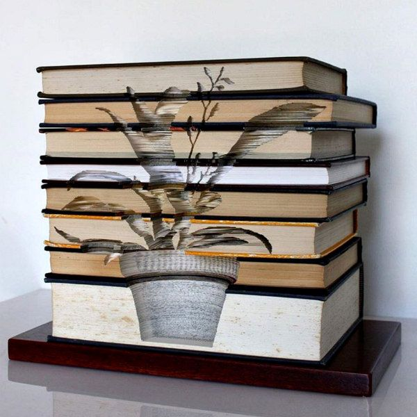 stack of old hardcover books on wooden base with hand carved potted plant design cut across open edges