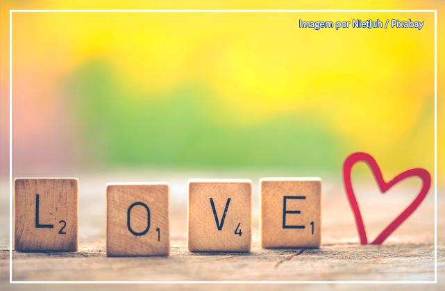 """A imagem mostra quatro peças de madeira com letras inscritas. As peças formam a palavra """"LOVE"""". Ao lado das peças, um pequeno coração vermelho feito de arame."""