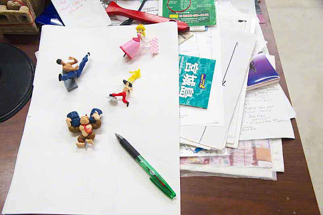 Toy characters, blank paper and pen, messy desk