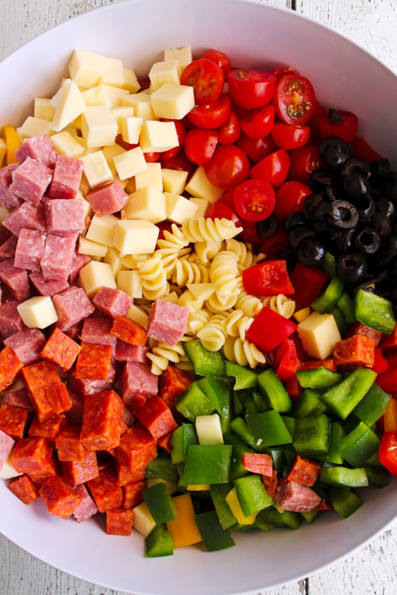 Top view of Manhattan Deli Pasta Salad ingredients unmixed in a large white bowl on a white wooden background.