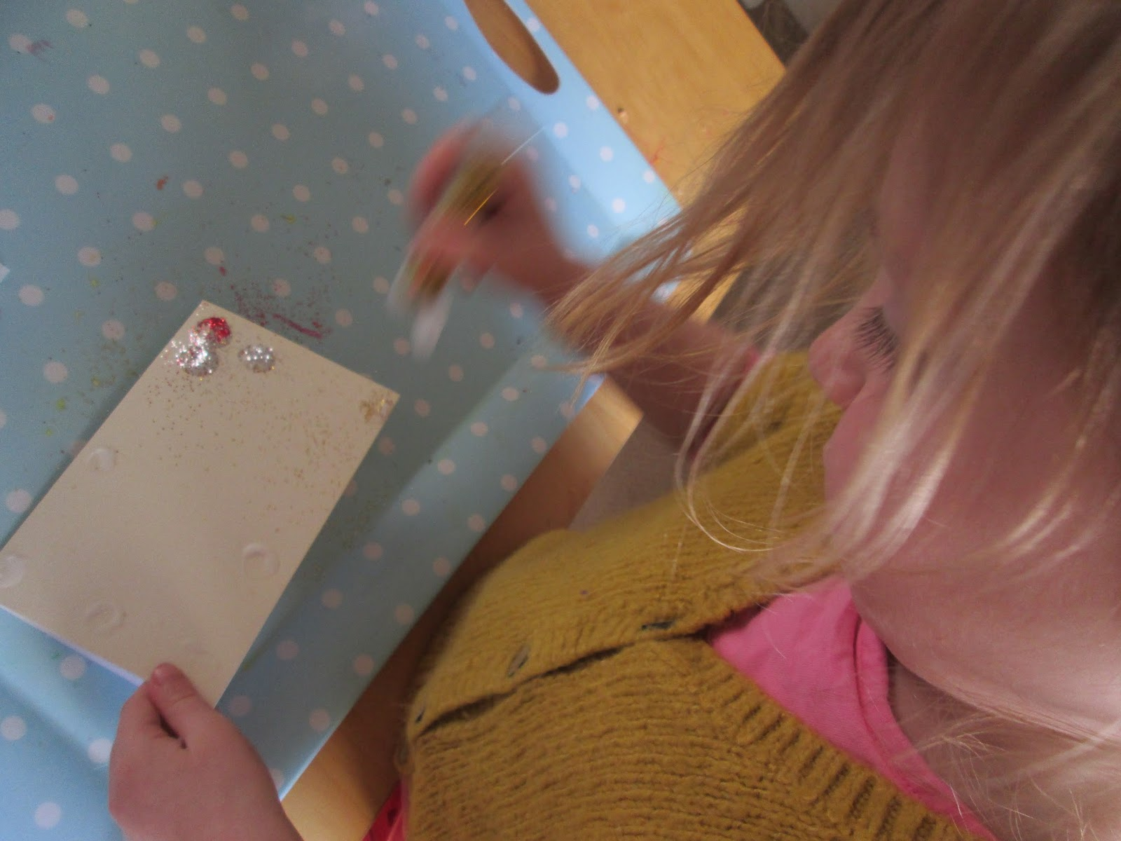 Lily shaking glitter all over the card