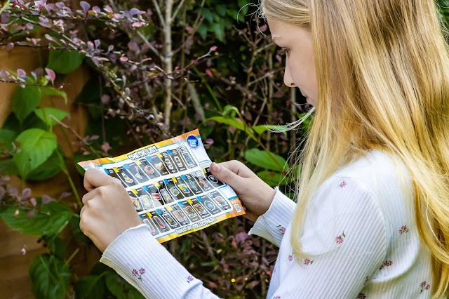 A young girl looking at one side of the Micro Toy Box Collectors Check List