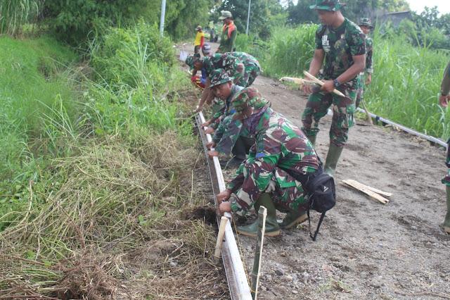 "Mojokerto, - Memasuki hari kedua, kegiatan  TMMD Ke-107 TA. 2020 di Wilayah Kodim 0815/Mojokerto personel yang tergabung dalam Satgas TMMD 107, langsung mengerjakan sasaran fisik di Desa Mojolebak Kecamatan Jetis, Kabupaten Mojokerto, Jawa Timur, Selasa (17/03/2020).  Pada TMMD Ke-107 terdapat sejumlah sasaran fisik yang dikerjakan, salah satunya yaitu pengerjaan peningkatan kualitas jalan lingkungan yang menghubungkan Dusun Mojolebak dan Dusun Mojogeneng Desa Mojolebak.   Sejatinya pengerjaan jalan lingkungan dengan volume 580 meter x 3 meter ini sudah berlangsung sejak Senin (16/03) kemarin dan menjadi salah satu obyek peninjauan Aster Kasdam V/Brawijaya Kolonel Inf Singgih Pambudi Arinto, S.IP., MM.  Dansatgas TMMD 107 Kodim 0815/Mojokerto Letkol Inf Dwi Mawan Sutanto, SH., mengungkapkan, TMMD sebagai salah satu wujud Operasi Bakti TNI dan merupakan program terpadu lintas sektoral antara TNI, Polri, Kementerian/LPNK, dan Pemda serta komponen bangsa lainnya yang dilaksanakan secara terintegrasi bersama masyarakat guna meningkatkan kegiatan pembangunan di pedesaan.    Peningkatan kualitas jalan lingkungan ini, bertujuan untuk meningkatkan akses masyarakat setempat sehingga lebih memudahkan dalam pendistribusian barang, jasa dan lalu lintas manusia.  ""Dengan adanya perbaikan dan peningkatkan infrastruktur jalan ini, diharapkan dapat memperlancar transportasi dan lebih menggairahkan perekonomian warga setempat,"" tegas Dansatgas.  Masih kata pria yang sehari-hari menjabat Dandim 0815/Mojokerto ini, dengan adanya pembangunan infrastruktur ini, tentunya akan meningkatkan Desa Canggu yang saat ini masih desa berkembang menjadi desa maju dan sejahtera.   Pantauan di lapangan, gabungan personel Satgas TMMD bahu membahu bersama masyarakat mengerjakan sasaran fisik sesuai dengan pembagian tugas masing-masing. Tampak jelas, TMMD ini menjadi salah satu sarana untuk memperkokoh kemanunggalan TNI – Rakyat. (Jayak)"