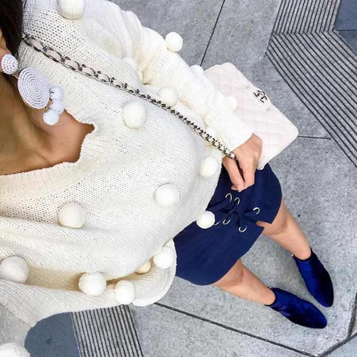 madewell pom pom sweater, lace up skirt, chanel mini flap, pom pom earrings, velvet ankle booties