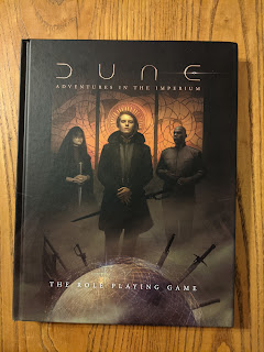 A photo of the core rulebook, which features art depicting Paul Atreides, a Bene Gesserit, and a Mentat.