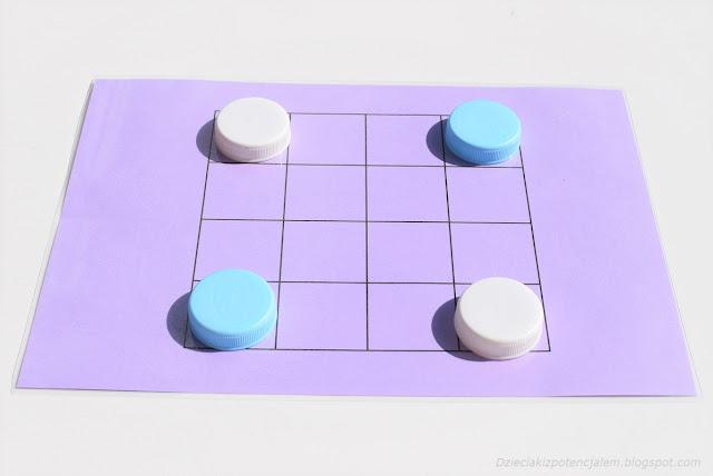 na zdjęciu fioletowa plansza 4x4 oraz po dwa pionki zrobione z nakrętek w kolorze błękitnym i białym