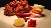 Serving Chicken Kandhari kebab, beetroot and pomegranate on side of the plate