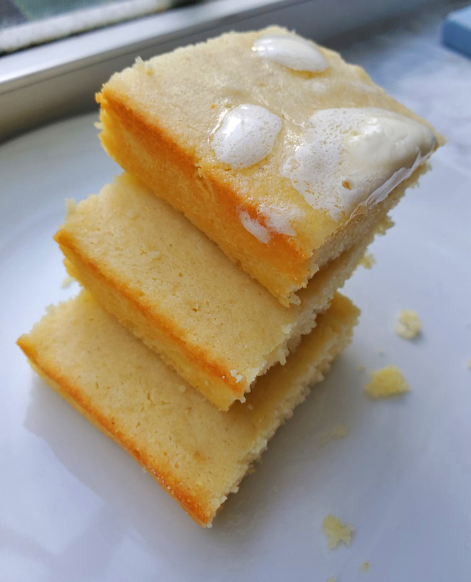this is a basic cornbread recipe slathered with butter on a white plate triple stacked
