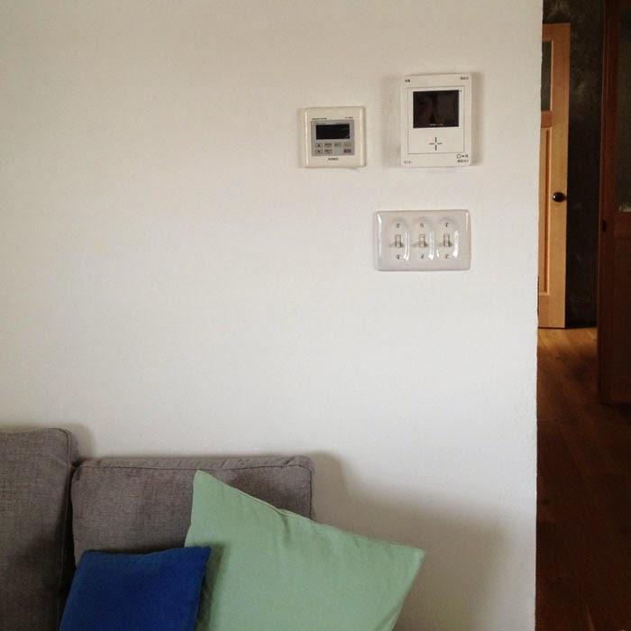 リノベーションマンションの陶器製スイッチとインターホンのモニターとソファ