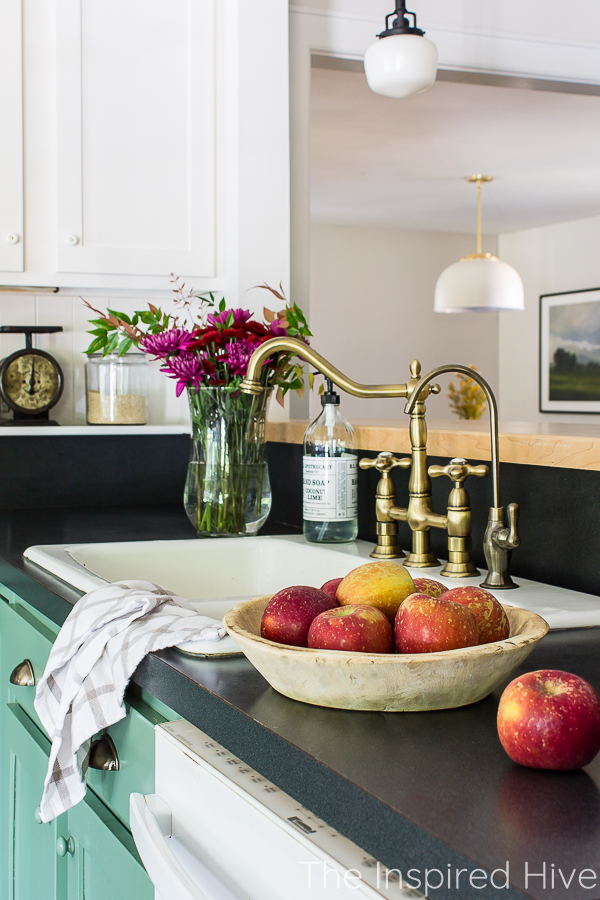 Farmhouse kitchen sink with fall florals and bowl of red apples on the counter