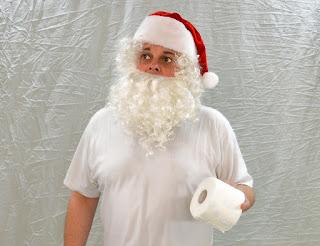 白い背景。前面に立つのは,サンタの帽子をかぶった人間。何故か,トイレットペーパーを左手に持ち,惚けた表情で遠くを見つめている写真。