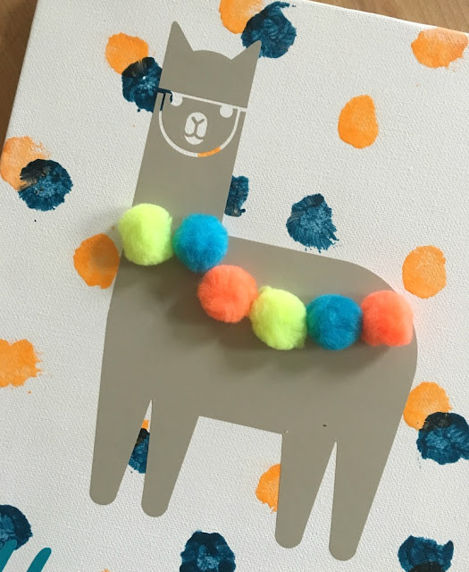 Add a touch of whimsy to a nursery with DIY painted llama pom pom wall art made with vinyl and Cricut.