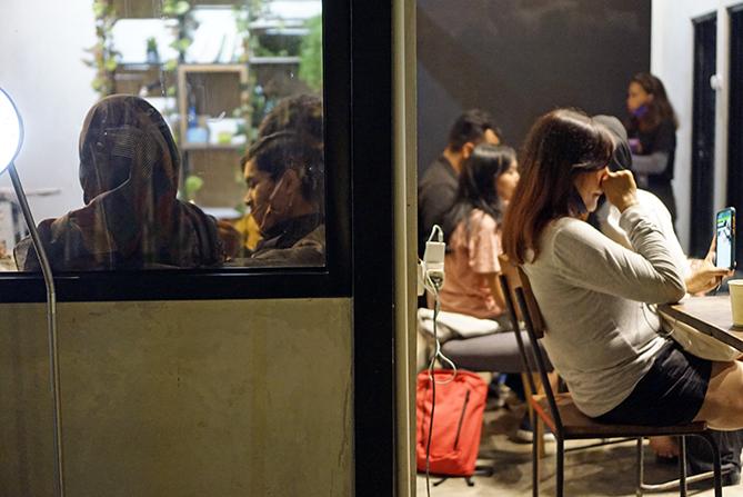 Pengunjung menikmati waktu malam di kedai kopi