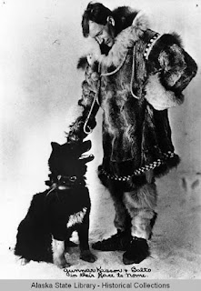 Man in fur parka and leggings with a dog