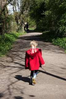 Little girl in red coat on a woodland path