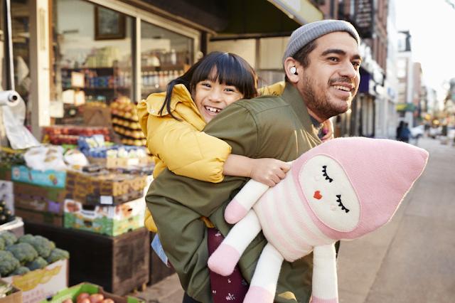 Mann trägt ein lachendes Kind auf dem Rücken und hat Pixel Buds im Ohr