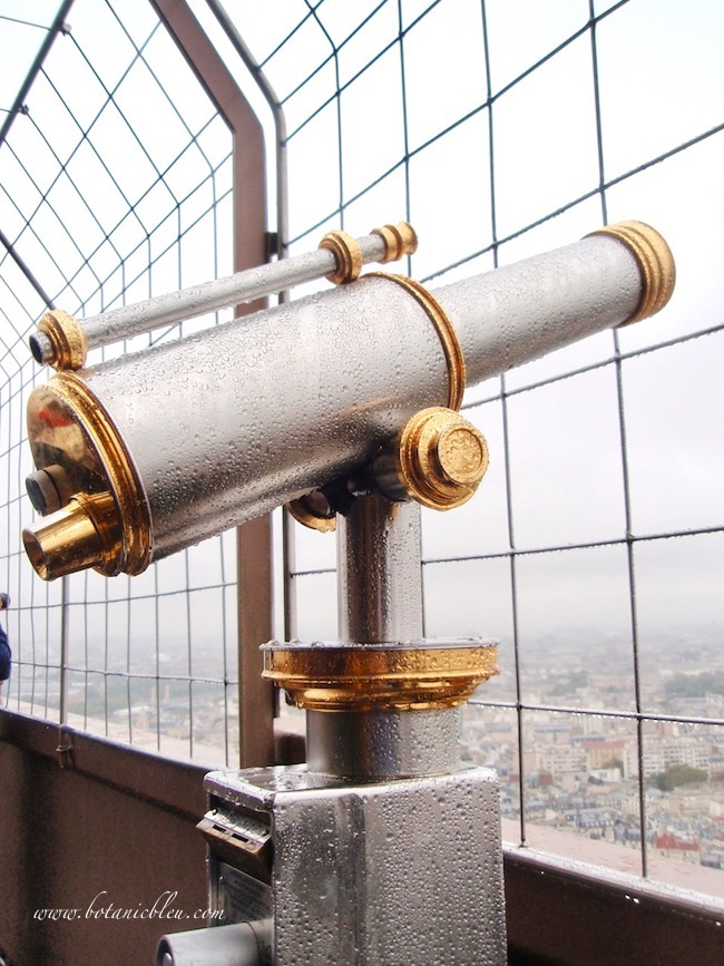 Eiffel Tower gold and silver telescopes are beautiful even when dripping with rain under misty Paris skies