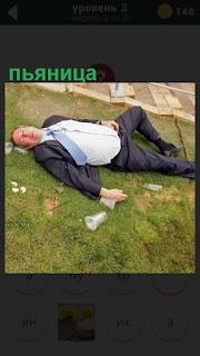 мужчина в пьяном виде в костюме лежит на траве раскинув руки