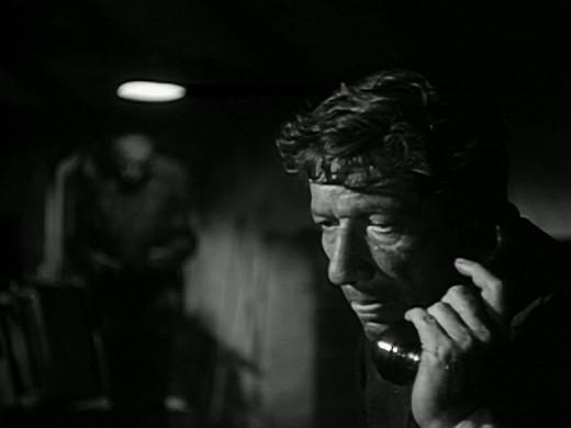 Bob Kraft (Richard Boone) answers the phone in I Bury the Living, 1958
