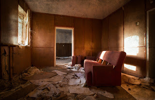A room in a trailer home with a ratty orange couch and papers strewn everywhere.