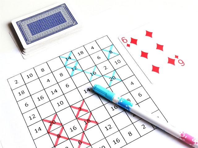 na zdjęciu plansza do gry trzy w rzędzie w formie kwadratu 8x8 z wpisanymi wynikami mnożenia w poszczególnych polach planszy, kilka pól jest skreślonych czerwonym pisakiem, obok leży pisak