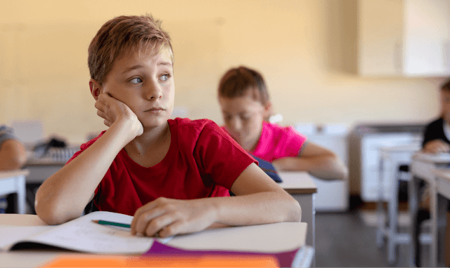 Photo of boy looking hesitant in a classroom with books open on his desk.