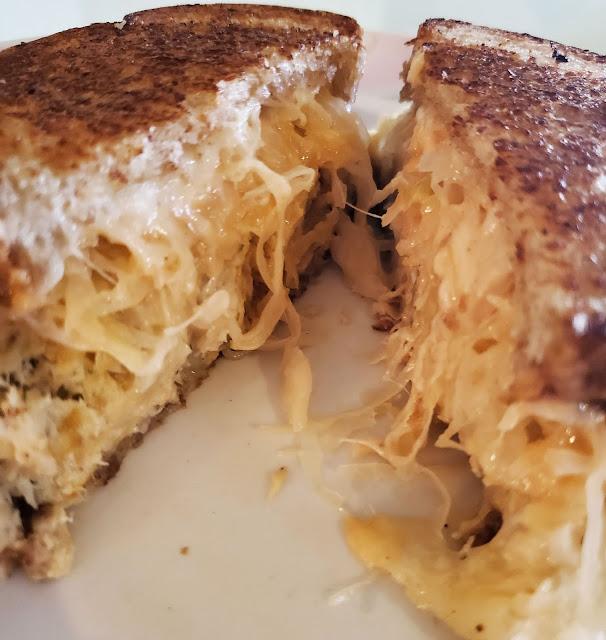 Tilapia Reuben sandwich cut in half on a plate