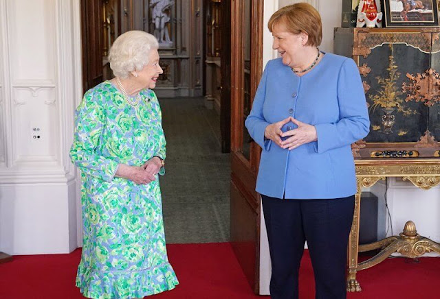 Queen Elizabeth wore a blue and green floral dress with an diamond Cambridge Emerald Cluster Brooch. Anello and Davide of Kensington shoes