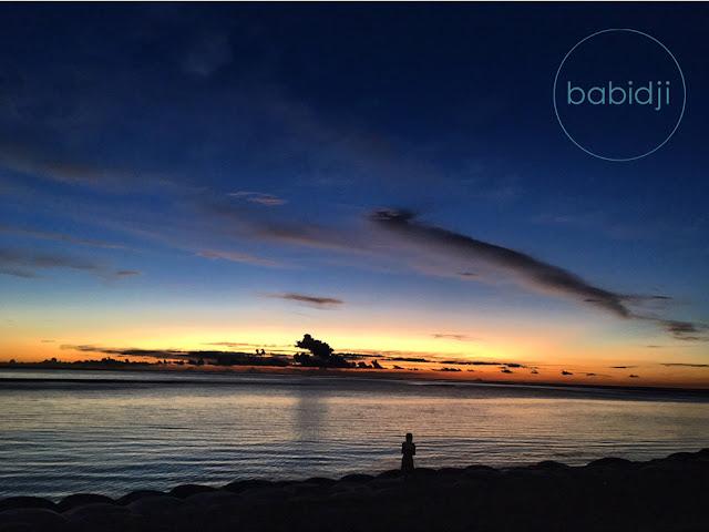 petite fille qui regarde l'océan au sunset sur la plage de la Preneuse à l'Île Maurice