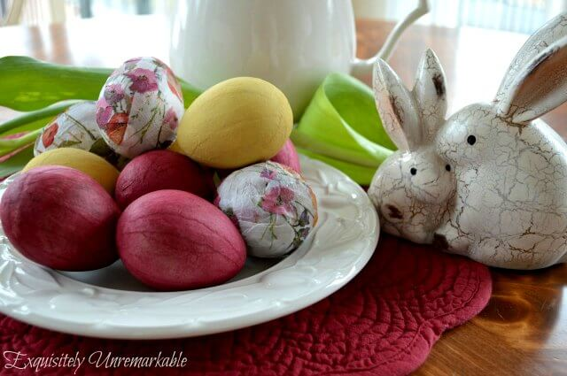 Decoupaged and painted Easter eggs on white plate next to flowers and faux bunnies