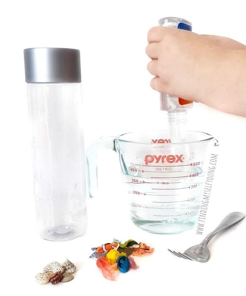 adding glue to a sensory bottle