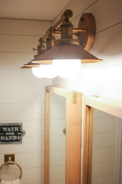 Swapping the light fixture is an easy way to update a boring bathroom