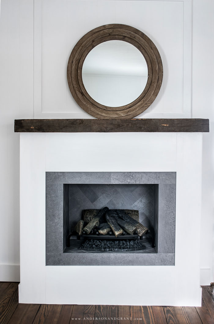 White fireplace with round wood mirror
