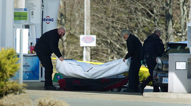 Image Attribute: Workers with the medical examiner's office remove a body from a gas station in Enfield, Nova Scotia, April 19, 2020. / Source: AP