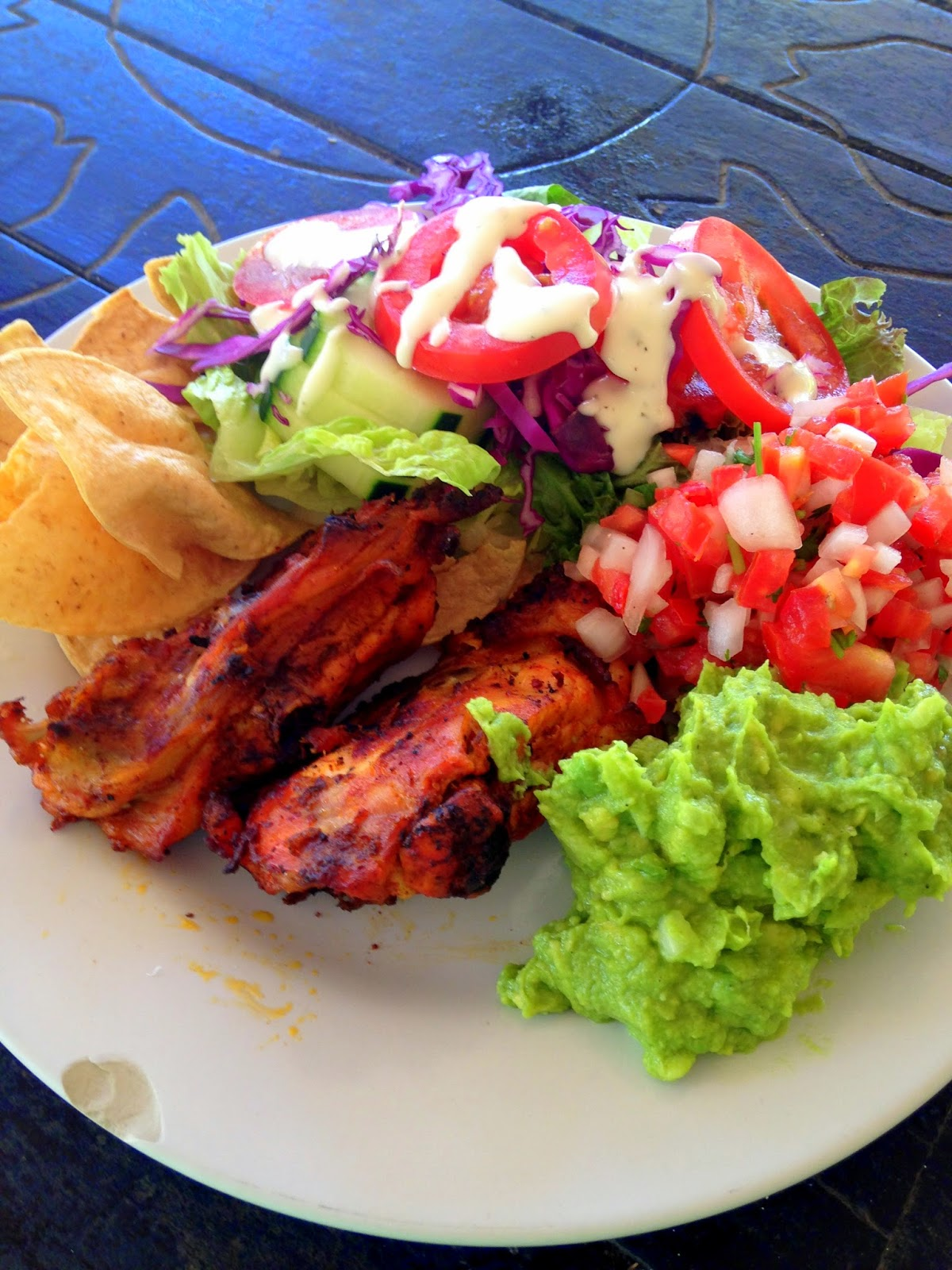 Mexican buffet with chips, pico de gallo, guacamole, barbecue chicken, and salad